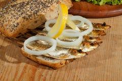 Κλυπέες, που καπνίζονται, σαλάτα, λεμόνι, κρεμμύδια, ολόκληρο ψωμί σίτου Στοκ Φωτογραφία