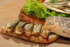 Κλυπέες, που καπνίζονται, σαλάτα, λεμόνι, κρεμμύδια, ολόκληρο ψωμί σίτου Στοκ Εικόνα