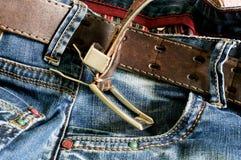 Κλωστοϋφαντουργικό προϊόν: τζιν παντελόνι με μια καφετιά ζώνη δέρματος Στοκ εικόνα με δικαίωμα ελεύθερης χρήσης