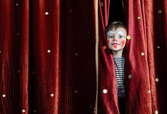 Κλόουν αγοριών που κοιτάζει αδιάκριτα μέσω των σκηνικών κουρτινών Στοκ εικόνα με δικαίωμα ελεύθερης χρήσης