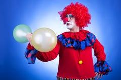 Κλόουν με τα μπαλόνια διαθέσιμα στο μπλε υπόβαθρο Στοκ φωτογραφίες με δικαίωμα ελεύθερης χρήσης