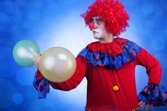 Κλόουν με τα μπαλόνια διαθέσιμα στο μπλε υπόβαθρο Στοκ Εικόνα