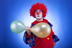 Κλόουν με τα μπαλόνια διαθέσιμα στο μπλε υπόβαθρο Στοκ εικόνες με δικαίωμα ελεύθερης χρήσης