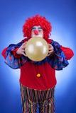 Κλόουν με το μπαλόνι στο κόκκινο κοστούμι στο μπλε υπόβαθρο Στοκ Εικόνες