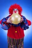 Κλόουν με ballon στα χέρια στο μπλε υπόβαθρο Στοκ Φωτογραφία