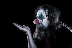Κλόουν φρίκης με το άσχημο πρόσωπο που κοιτάζει στο copyspace, μαύρο backgrou Στοκ Φωτογραφίες
