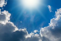 Λάμποντας ήλιος στο υπόβαθρο του μπλε ουρανού και των άσπρων σύννεφων Στοκ Εικόνα