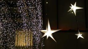 Λάμποντας αστέρια, φω'τα λαμπυρίσματος, γιρλάντα στην πρόσοψη ενός κτηρίου Διακοσμήσεις οδών Χριστουγέννων, νέο έτος απόθεμα βίντεο