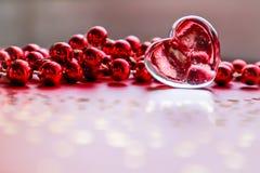 Λάμποντας διαφανής καρδιά και κόκκινες χάντρες Τέλειο υπόβαθρο ευχετήριων καρτών ημέρας βαλεντίνων στοκ φωτογραφίες