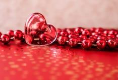 Λάμποντας διαφανής καρδιά και μια ομάδα κόκκινων χαντρών Τέλειο υπόβαθρο ευχετήριων καρτών ημέρας βαλεντίνων στοκ εικόνες με δικαίωμα ελεύθερης χρήσης