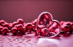 Λάμποντας διαφανής καρδιά και μια ομάδα κόκκινων χαντρών Υπόβαθρο ευχετήριων καρτών ημέρας του τέλειου βαλεντίνου Οριζόντια εικόν στοκ εικόνες