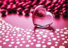 Λάμποντας διαφανής καρδιά και μια ομάδα κόκκινων χαντρών Υπόβαθρο ευχετήριων καρτών ημέρας του τέλειου βαλεντίνου Οριζόντια εικόν στοκ εικόνα