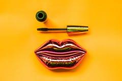 λάμποντας ρόδινα χείλια και mascara στο φωτεινό κίτρινο υπόβαθρο, makeup και την έννοια ομορφιάς στοκ φωτογραφία