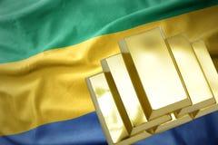 Λάμποντας χρυσές ράβδοι στη σημαία της Γκαμπόν Στοκ Φωτογραφία