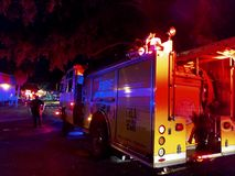 Λάμψη φω'των πυροσβεστικών οχημάτων στην πανεπιστημιούπολη κολλεγίου καθώς σβήνουν την πυρκαγιά τη νύχτα στοκ εικόνα με δικαίωμα ελεύθερης χρήσης