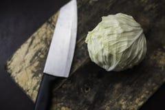 Λάχανο και μαχαίρι σε έναν τεμαχίζοντας πίνακα Στοκ Εικόνες