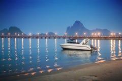 Λέμβος ταχύτητας που βάζει στην όμορφη θάλασσα κοντά στην παραλία άμμου city lights night scene αντανάκλαση του φωτός στην επιφάν Στοκ εικόνες με δικαίωμα ελεύθερης χρήσης