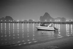 Λέμβος ταχύτητας που βάζει στην όμορφη θάλασσα κοντά στην παραλία άμμου city lights night scene αντανάκλαση του φωτός στην επιφάν Στοκ φωτογραφία με δικαίωμα ελεύθερης χρήσης