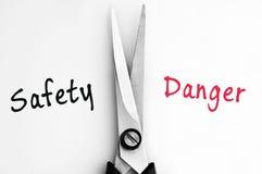 Λέξεις ασφάλειας και κινδύνου με το ψαλίδι στη μέση στοκ εικόνες