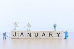 Λέξεις Ιανουαρίου με το μικροσκοπικό εργαζόμενο ανθρώπων Στοκ φωτογραφίες με δικαίωμα ελεύθερης χρήσης