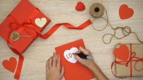 Λέξη αγάπης γραψίματος χεριών στη ευχετήρια κάρτα που βρίσκεται στον πίνακα με τα κιβώτια δώρων τεχνών απόθεμα βίντεο
