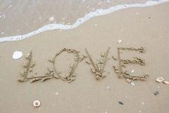 Λέξη αγάπης στην παραλία με το κύμα Στοκ φωτογραφία με δικαίωμα ελεύθερης χρήσης