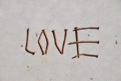 Λέξη ΑΓΑΠΗΣ που διαμορφώνεται από τα σκουριασμένα καρφιά στο γκρίζο συγκεκριμένο υπόβαθρο Στοκ Φωτογραφίες