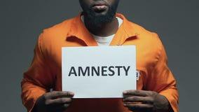 Λέξη αμνηστίας στο χαρτόνι στα χέρια του αφροαμερικανού φυλακισμένου, συγχώρεση απόθεμα βίντεο