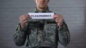Λέξη αφοπλισμού που γράφεται στο σημάδι στα χέρια του αρσενικού στρατιώτη, τέλος του πολέμου, ειρήνη απόθεμα βίντεο