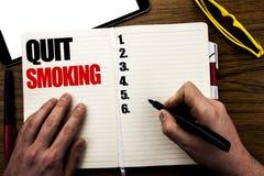 Λέξη, γράψιμο εγκαταλειμμένο κάπνισμα Επιχειρησιακή έννοια για τη στάση για το τσιγάρο που γράφεται στο βιβλίο, ξύλινο υπόβαθρο μ Στοκ Εικόνες