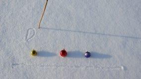 Λέξη Δεκέμβριος γραψίματος στις σφαίρες χιονιού και Χριστουγέννων απόθεμα βίντεο