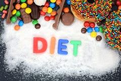 Λέξη διατροφής που γράφεται στη σκόνη άσπρης ζάχαρης με τα διάφορα γλυκά στοκ φωτογραφία