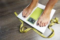 Λέξη διατροφής στην οθόνη κλίμακας βάρους με τα πόδια γυναικών και την ταινία μέτρησης Στοκ Φωτογραφία