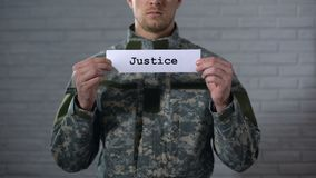 Λέξη δικαιοσύνης που γράφεται στο σημάδι στα χέρια του αρσενικού στρατιώτη, Στρατοδικείο, δικαστήριο φιλμ μικρού μήκους