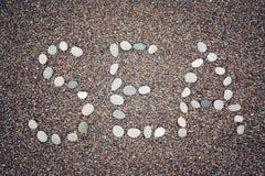 Λέξη «θάλασσας» στην άμμο Γραπτός με τα χαλίκια ηλικίας φωτογραφία Στοκ Εικόνες