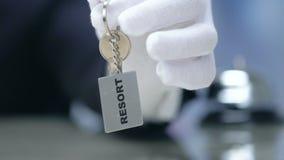 Λέξη θερέτρου στο keychain στο θηλυκό χέρι διοικητών, φιλική ουσία, υπηρεσία φιλμ μικρού μήκους