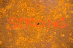 Λέξη ισχυρή που χρωματίζει στο υπόβαθρο με τη σκουριά στο χάλυβα Στοκ εικόνα με δικαίωμα ελεύθερης χρήσης