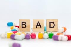 Λέξη ΚΑΚΗ με το ζωηρόχρωμο χάπι στο λευκό Στοκ Φωτογραφίες