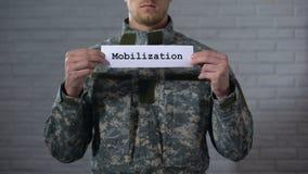Λέξη κινητοποίησης που γράφεται στο σημάδι στα αρσενικά χέρια στρατιωτών, που προετοιμάζονται για τον πόλεμο απόθεμα βίντεο