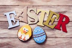 Λέξη Πάσχα και μπισκότα που διακοσμούνται ως αυγό Πάσχας και νεοσσός Στοκ Εικόνες