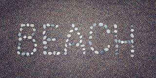 Λέξη «παραλιών» στην άμμο Γραπτός με τα χαλίκια ηλικίας φωτογραφία Στοκ φωτογραφία με δικαίωμα ελεύθερης χρήσης