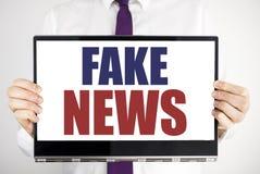 Λέξη, πλαστές ειδήσεις γραψίματος Η επιχειρησιακή έννοια για τη δημοσιογραφία εξαπάτησης που γράφτηκε στην εκμετάλλευση lap-top τ στοκ εικόνες