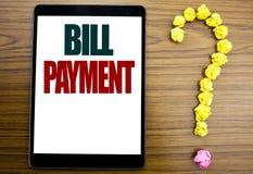 Λέξη, πληρωμή γραψίματος Μπιλ Η επιχειρησιακή έννοια για την τιμολόγηση πληρώνει τις δαπάνες που γράφονται στην ταμπλέτα, ξύλινο  στοκ φωτογραφία με δικαίωμα ελεύθερης χρήσης