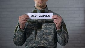 Λέξη πολεμικών θυμάτων που γράφεται στο σημάδι στα αρσενικά χέρια στρατιωτών, διανοητηκή διαταραχή, τραύμα απόθεμα βίντεο