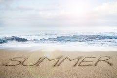 Λέξη που γράφεται θερινή στην παραλία άμμου με το φως του ήλιου σύννεφων ουρανού Στοκ φωτογραφία με δικαίωμα ελεύθερης χρήσης