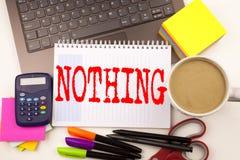 Λέξη που δεν γράφει τίποτα στο γραφείο με το lap-top, δείκτης, μάνδρα, χαρτικά, καφές Επιχειρησιακή έννοια για την αντίφαση τίποτ στοκ εικόνα