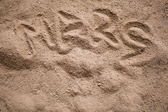 Λέξη του Άρη που χρωματίζεται σε μια σκοτεινή άμμο με τις προσκρούσεις Στοκ Φωτογραφία