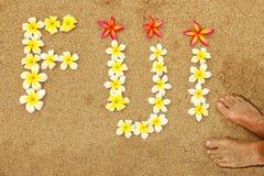 Λέξη Φίτζι που γράφονται σε μια παραλία με τα λουλούδια plumeria Στοκ Εικόνες