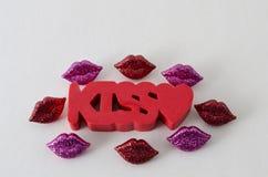 Λέξη φιλιών στο κόκκινο με μια μικρή καρδιά και μικρά shinny κόκκινα και πορφυρά χείλια στοκ φωτογραφίες