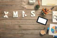 Λέξη - Χριστούγεννα στο γραφείο γραφείων με τα αντικείμενα γραφείων Στοκ Φωτογραφίες